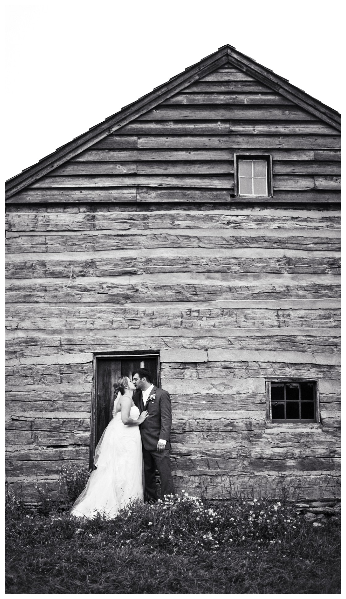Classic black and white image of wedding couple at the door of a log cabin